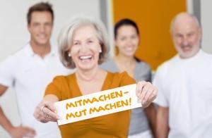Gruppe von Leuten. Eine ältere Frau hälltz ein Schild 'Mitmachen - Mut machen''